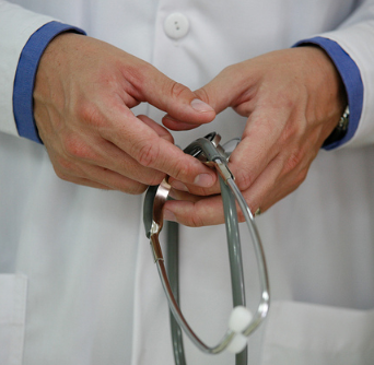 doctor's hands holding stethoscope