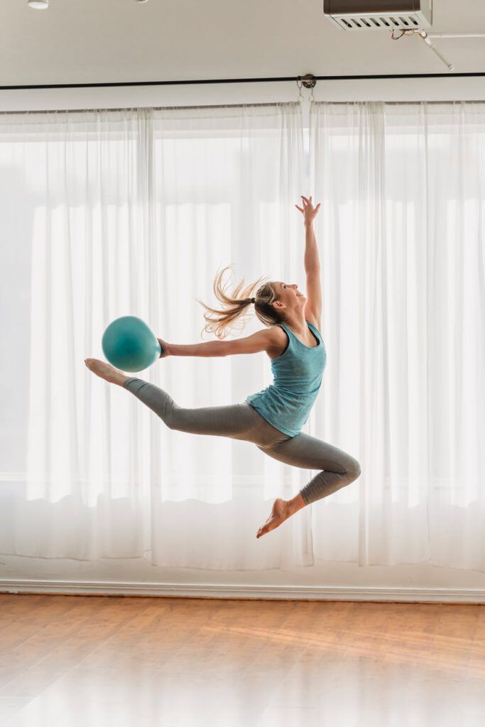 fit woman doing gymnastic exercise with fit ball